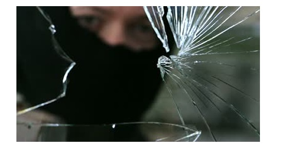burglar breaking into house by smashing window glass