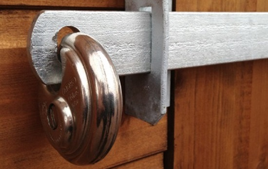 a good security lock securing an external garden shed at the rear of a property in London