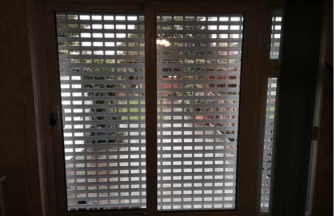 RSG5100 domestic shutter with 77mm punched laths in a brick bond style securing rear patio door in Greenford, Middlesex.